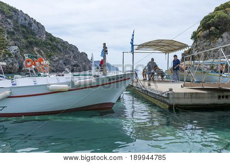 PALEOKASTRITSA, GREECE - MAY 15: Boats waiting for tourists who want to explore the caves on the Ionian Sea coast on May 15, 2017 in Paleokastritsa resort, Corfu island in Greece.