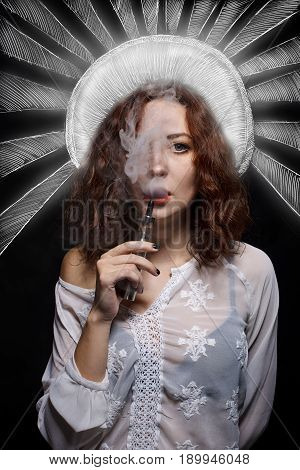 Beautiful woman smoking electronic cigarette over black background