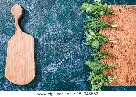 Fresh cilantro, tarragon, dill, oregano, thyme and lemon balm potherbs and cutting board ready for cooking over dark blue spotty background. Top view