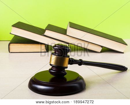 Books and wooden judge gavel on background of green wall. Law concept