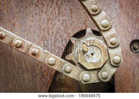 Old rusted sprocket and chain at an abandoned mine