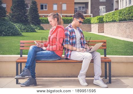 Beautiful young couple sitting on bench in the park and using modern digital devices. Social gathering problems