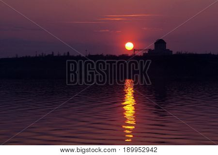 Crimson sunset at Voronezh water reservoir. Silhouette of nuclear power plant