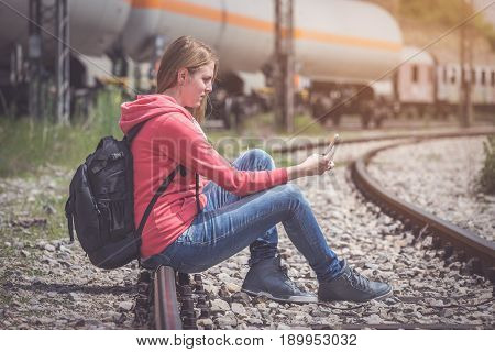 Traveler sitting on rail way and looking at mobile phone