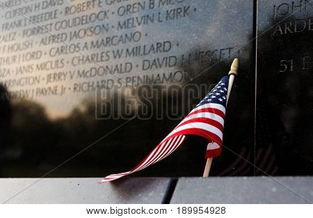 Washington DC, USA, 15th April 2017 - Editorial photograph of American Flag leaning against Vietnam War Memorial Wall commemorating over 58000 military personnel who served in the Vietnam War