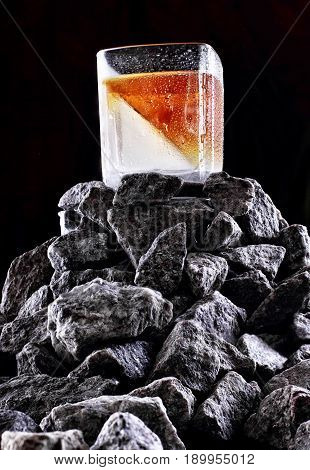 Glass Of Whiskey With Half Glass Ice .on Stone Mountain .creative Photo.advertising Shot