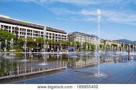 NICE, FRANCE - JUNE 4, 2017: A view of the reflecting pool of the Promenade du Paillon in Nice, France. This pool in the large public park has 128 water jets, that delight children