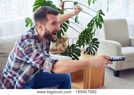 Mid shot of attractive man cheering and switching channel with remote control