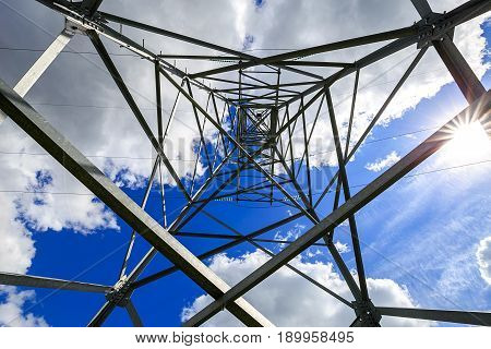The electricity transmission pylon in daytime outdoors. Electricity tower standard overhead power line transmission tower on the background blue sky and white cloud.