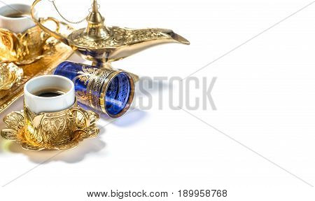 Golden coffee cups and arabic lantern on white background. Oriental hospitality concept