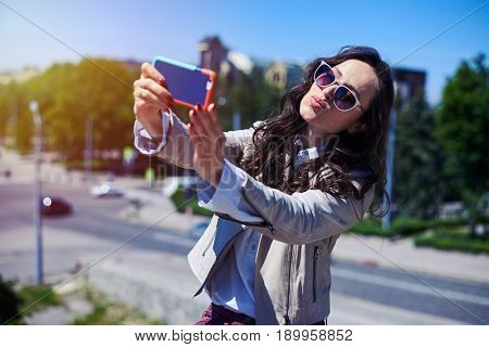 Mid shot of nice female taking selfie in front of city panorama