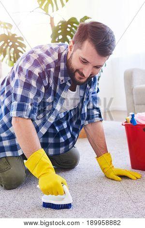 Vertical of smiling man in gloves brushing carpet in spacy room