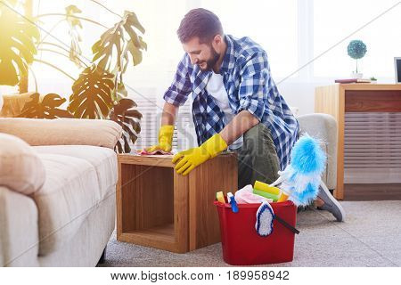 Wide shot of muscular bachelor mopping attentively coffee table