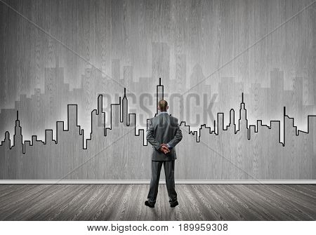 Businessman standing with back in concrete room with city silhouette on wall