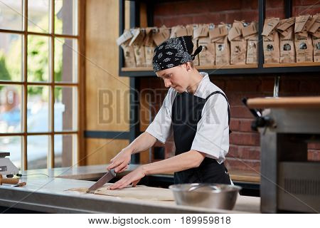 Woman slicing noodles in cafe. Horizontal indoors shot of woman working and slicing the knead in kitchen of restaurant. Making pasta. Making pasta in restaurant.