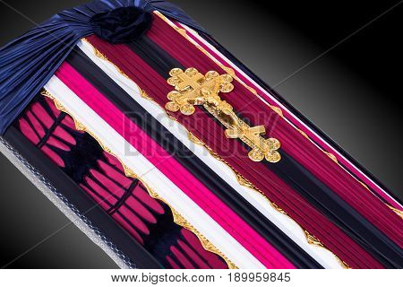 closed coffin covered with pink and blue cloth decorated with Church gold cross isolated on gray luxury background. Ritual objects for burial. Surrender body dust of the earth. Close-up details.