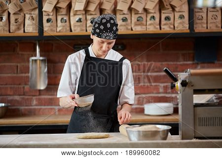 Female cook in uniform putting floor on dough while cooking pasta in cafe. Making pasta. Making pasta in restaurant. Woman add flour to dough