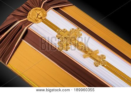closed coffin covered with brown and beige cloth decorated with Church gold cross isolated on gray luxury background. Ritual objects for burial. Surrender body dust of the earth. Close-up details.