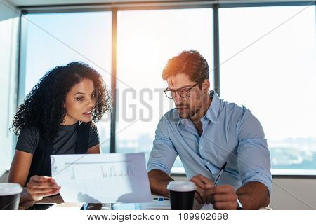 Young woman entrepreneur showing a paper to her business partner while discussing business plans. Young man and woman sitting at table in office analyzing business performance.