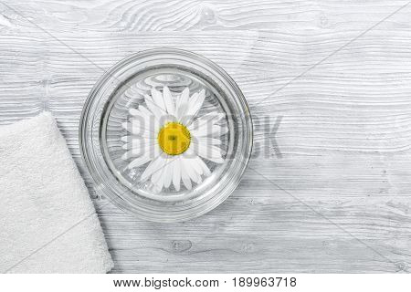 Spa composition on wooden desk with chamomile and towel copyspase top view.