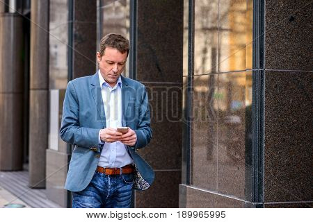 A middle age businessman walking next to the office building while using his smartphone
