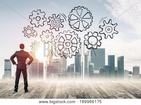 Back view of businessman looking at modern city and drawn gear mechanism