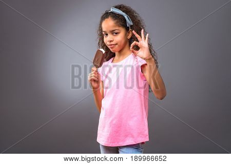 A young black teenage girl standing and holding an ice-cream while showing perfect hand sign