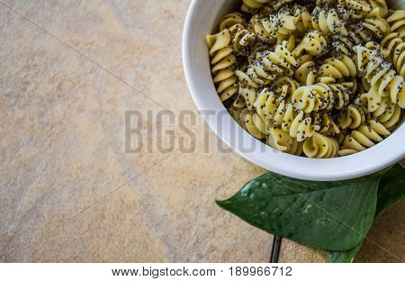 Rotini pasta swirls topped with black chia seeds in a white bowl on brown stone table. Copyspace on left side of food items.