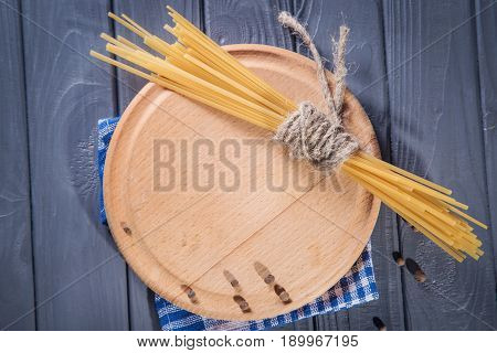 empty wooden plate with dry macaroni on grey background
