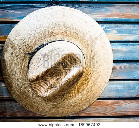 Straw cowboy hat hanging on blue weathered plank wall with vertical slats. Background. Copyspace.