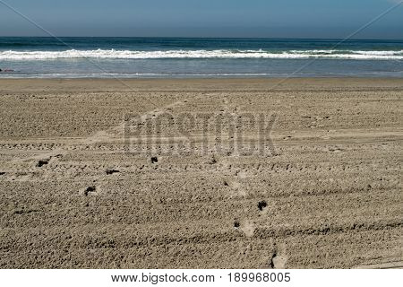 Sandy beach with footprints running towards ocean waves. Nobody in photo