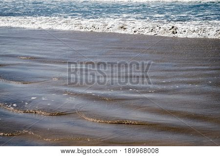 Ocean whitecap waves and gentle rumbling waves approach a sandy beach. Copyspace.