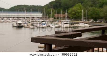 Wood balcony overlooking blurred river and boat marina with trees. Copyspace included in foreground.