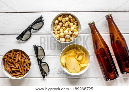 home party with TV watching, snacks, pop corn, chips and bread crumbs and beer on white background top view