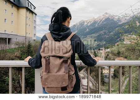 Austria. Bad Gastein - April 22, 2016: A traveler with a backpack is standing on a bridge overlooking the Alpine mountains
