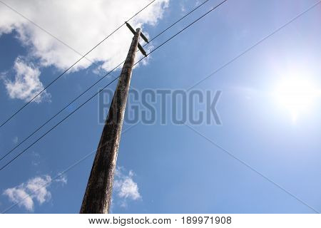 Tall wooden simple electrical pole and sun