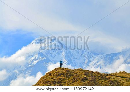 Young woman admires by Annapurna South Peak. Mountain Landscape in Annapurna region, Nepal, Himalaya.
