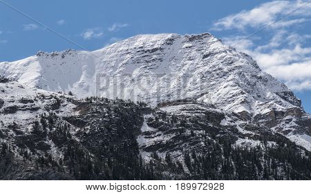 Blue skies over an immense mountain in Jasper National Park in Alberta Canada.