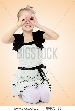 Beautiful little blonde girl dressed in a white short dress with black sleeves and a black belt.The girl folded her palms into a tube in the form of binoculars.