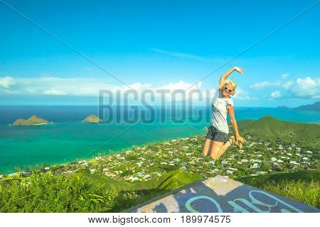 Hawaiian hiking. Happy woman celebrates one of most picturesque Oahu hiking trails in Hawaii. Joyful carefree hiker jumping during Lanikai Pillbox Hike. Lanikai Beach and Mokulua Islands on background