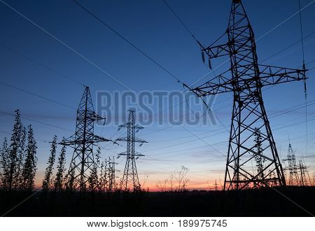 High voltage electricity pylons against sunset. Electric pole power lines and wires.