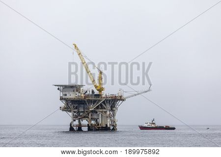 Ventura County, California, USA - June 4, 2017:  Active oil and gas rig with ship in the Santa Barbara Channel near the Southern California Coast.