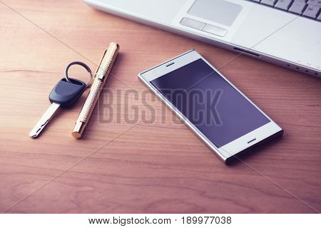 Chrome or silver smartphone. placed on a desk with pen, key, and laptop. Incandescent type lighting.