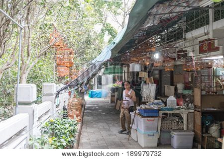 KOWLOON HONG KONG - APRIL 21 2017: Seller With Birdcage at Yuen Po Street Bird Garden in Kowloon Hong Kong.