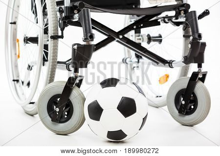 Wheelchair for invalid or disabled person and soccer ball white isolated