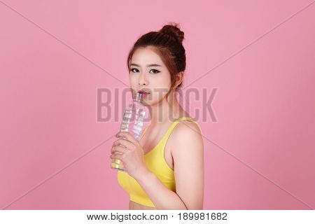 Positive Delighted Sportswoman Drinking Fresh Water With Isolated Pick Pastel Background