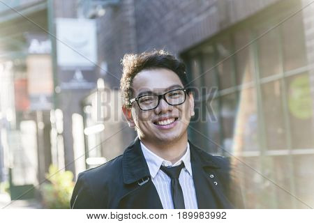 Young asian man wearing glasses on city street in late afternoon, intentional lens flare