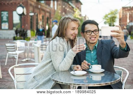 Two smiling young people taking a selfie with mobile device while sitting at outdoor cafe table on city street