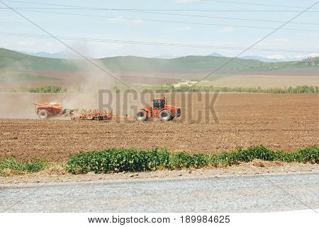 modern red tractor in the agricultural field. mechanism. Tractor plowing land. Harvester sowing wheat.