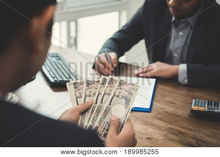 Businessman counting money Japanese yen banknotes while making an agreement with his partner in the office